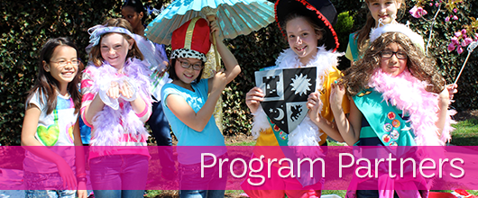 Purely decorative image of Girl Scouts in dress-up costumes with Program Partners on it